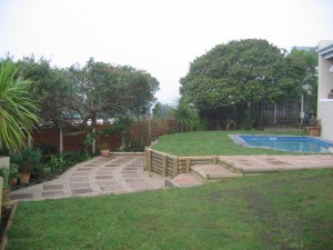 Paved entrance area and wooden retainer around pool
